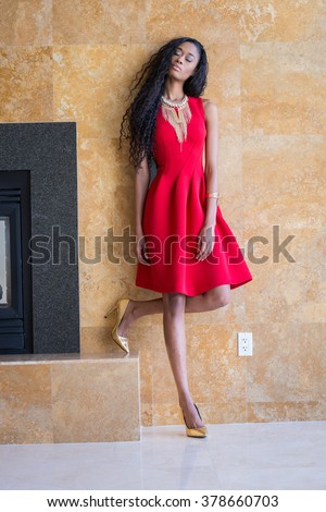 Portrait of a beautiful young black woman in red dress fashion outfit #378660703