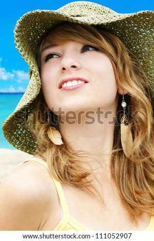 Portrait of a beautiful young blond woman on vacations at the beach with large straw sun hat.