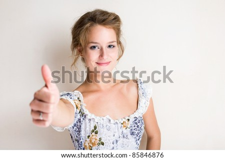 Portrait of a beautiful young blond woman showing thumbs up. - stock photo
