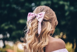 Portrait Of A Beautiful Young Blond Woman With Long Wavy Hair with pink bow. Back View.