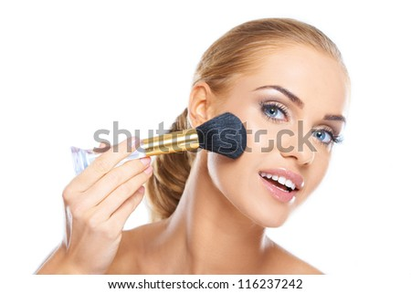 Portrait of a beautiful young blonde applying makeup to her face