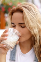 Portrait of a beautiful young blonde girl. White woman drinking coffee latte with closed eyes. Face close up view. Morning summer mood
