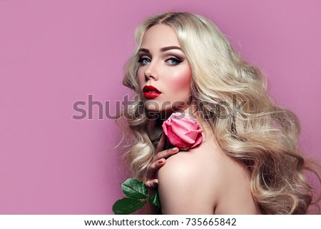 Portrait of a beautiful young blonde girl with a pink rose in hands on a pink background. Romance.