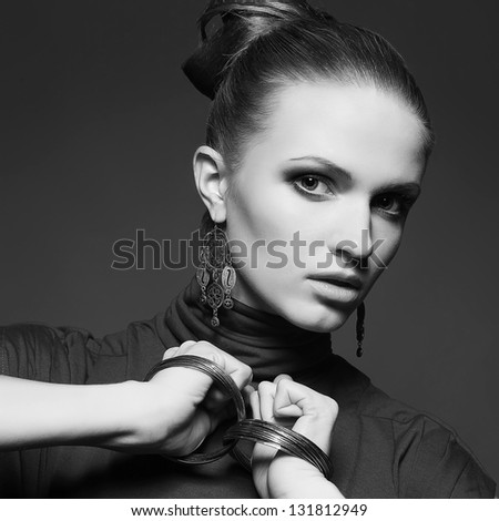 Portrait of a beautiful young blonde in grey dress wearing wristbands and posing over dark gray background. Perfect hairdo. Black and white (monochrome) studio shot