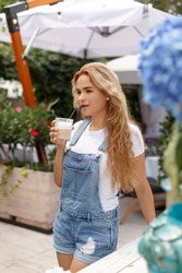 Portrait of a beautiful young blonde. White girl with long hair drinking coffee latte with enjoyment on the summer terrace of an Italian restaurant in the daytime.