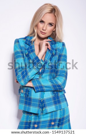 Portrait of a beautiful young blonde woman in a nice fashionable blue suit, glamour photo.