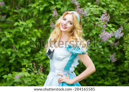 Portrait of a beautiful young blonde woman with long hair dressed as Alice in Wonderland. Girl on the nature near the lilac bushes. Soft focus