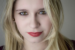 Portrait of a beautiful young blonde woman with red lipstick and intense gaze