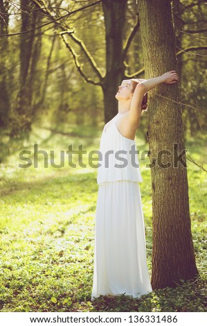 Portrait of a beautiful young bride in white wedding dress leaning against tree outdoors - stock photo