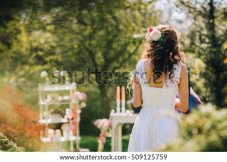 Portrait of a beautiful young bride wearing a slinky dress on the wedding ceremony. Portrait from the back. Decoration of ceremony. Copy space. Text place. Advertising place.