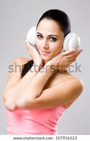 Portrait of a beautiful young brunette having fun with white headphones.