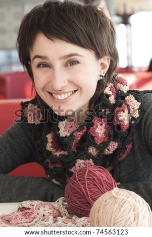 Portrait of a beautiful young brunette in a knitted scarf and bright with balls of thread