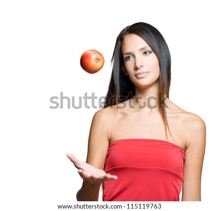 Portrait of a beautiful young brunette juggling fresh apple.