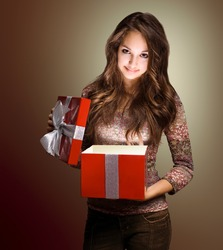Portrait of a beautiful young brunette peeking inside shiny red gift box in creative lighting.