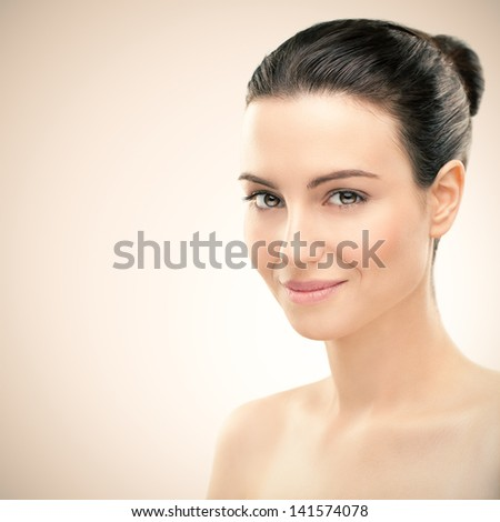 Portrait of a beautiful young brunette posing in front of a pink background.