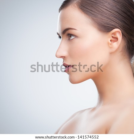 Portrait of a beautiful young brunette posing topless in front of a tray background. #141574552