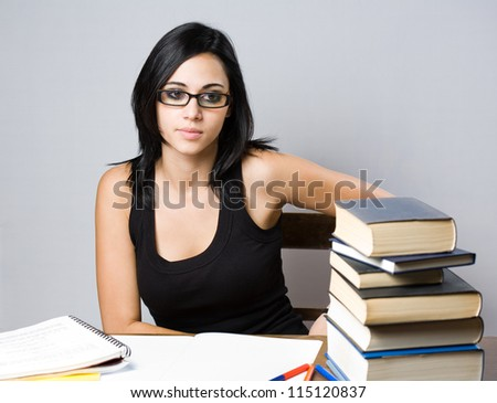 Portrait of a beautiful young brunette student with a large pile of books.