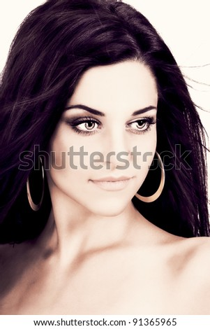 Portrait of a beautiful young brunette wearing golden earrings and strong make up