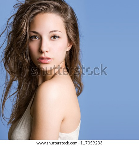 Portrait of a beautiful young brunette woman on blue background.