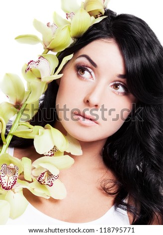portrait of a beautiful young brunette woman with an orchid, isolated on white background