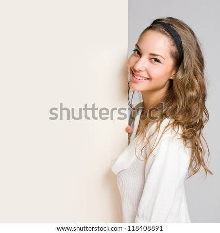 Portrait of a beautiful young brunette woman with blank billboard sheet.