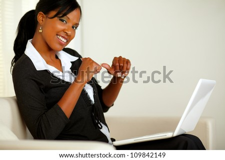 Portrait of a beautiful young business woman in front her laptop while pointing her fingers to her at home indoor