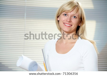 Portrait of a beautiful young business woman with the drawings in the office