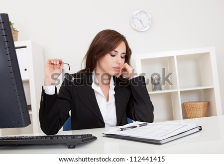 Portrait of a beautiful young businesswoman at desk thinking - stock photo