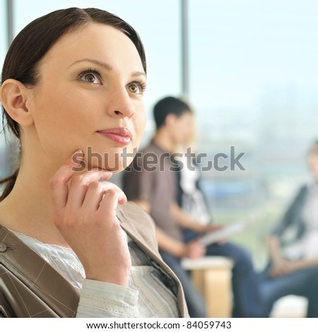 Portrait of a beautiful young businesswoman daydreaming. Office background.