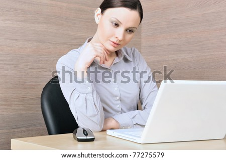 Portrait of a beautiful young businesswoman on the computer, reading. Office background.