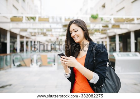 Portrait of a beautiful young businesswoman standing outside using mobile phone #332082275