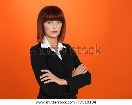 portrait of a beautiful, young, businesswoman, with her arms crossed, on orange background - stock photo