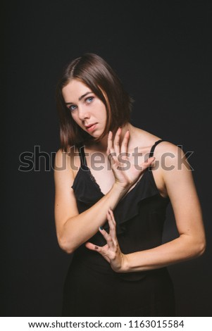 Portrait of a beautiful young Caucasian Caucasian woman 20 years old model with blue eyes natural make-up of hair on shoulder dancing hands posing on black isolated background in black lingerie. #1163015584