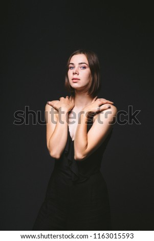 Portrait of a beautiful young Caucasian Caucasian woman 20 years old model with blue eyes natural make-up of hair on shoulder dancing hands posing on black isolated background in black lingerie. #1163015593