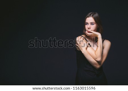 Portrait of a beautiful young Caucasian Caucasian woman 20 years old model with blue eyes natural make-up of hair on shoulder dancing hands posing on black isolated background in black lingerie. #1163015596