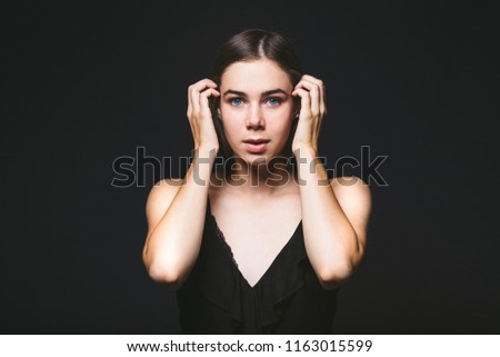 Portrait of a beautiful young Caucasian Caucasian woman 20 years old model with blue eyes natural make-up of hair on shoulder dancing hands posing on black isolated background in black lingerie. #1163015599