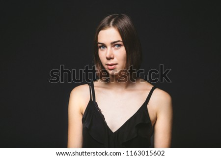 Portrait of a beautiful young Caucasian Caucasian woman 20 years old model with blue eyes natural make-up of hair on shoulder dancing hands posing on black isolated background in black lingerie. #1163015602