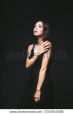 Portrait of a beautiful young Caucasian Caucasian woman 20 years old model with blue eyes natural make-up of hair on shoulder dancing hands posing on black isolated background in black lingerie. #1163015608