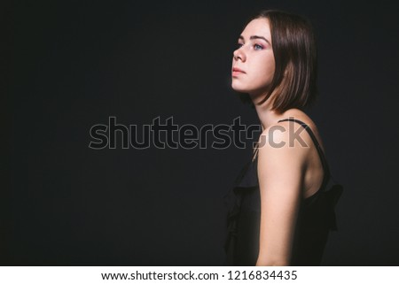 Portrait of a beautiful young Caucasian Caucasian woman 20 years old model with blue eyes natural make-up of hair on shoulder dancing hands posing on black isolated background in black lingerie. #1216834435