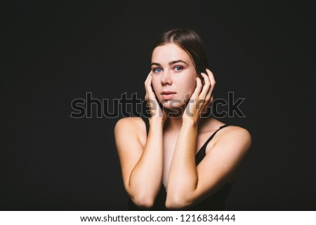 Portrait of a beautiful young Caucasian Caucasian woman 20 years old model with blue eyes natural make-up of hair on shoulder dancing hands posing on black isolated background in black lingerie. #1216834444