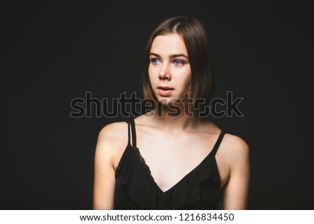 Portrait of a beautiful young Caucasian Caucasian woman 20 years old model with blue eyes natural make-up of hair on shoulder dancing hands posing on black isolated background in black lingerie. #1216834450