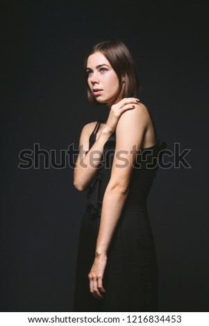 Portrait of a beautiful young Caucasian Caucasian woman 20 years old model with blue eyes natural make-up of hair on shoulder dancing hands posing on black isolated background in black lingerie. #1216834453