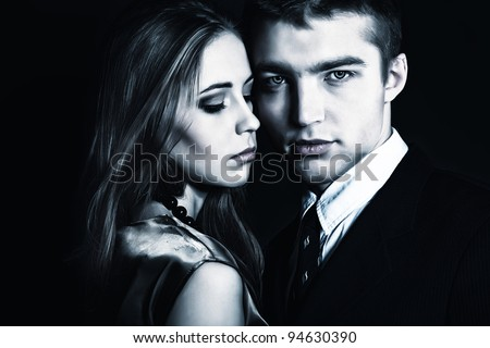Portrait of a beautiful young couple embracing with passion. Studio shot.