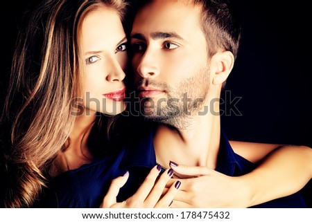 Portrait of a beautiful young couple in love posing at studio over dark background.