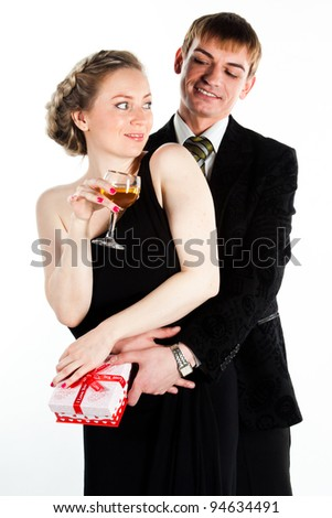Portrait of a beautiful young couple with glasses of wine and a gift box with a red bow