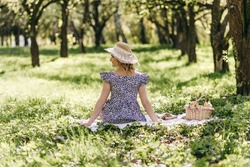 Portrait of a beautiful young curly blond woman in a wicker straw hat and dress with flowers sitting on a white plaid with a basket of fruits in a green park. Picnic, nature, beauty, summer.