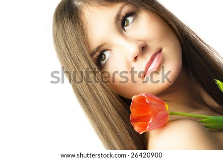 portrait of a beautiful young dreamy woman with a tulip against white background