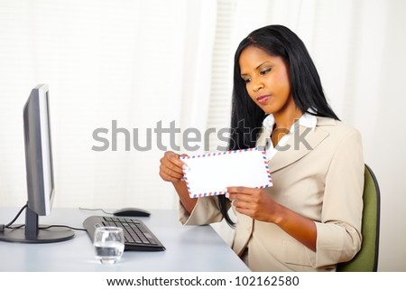 Portrait of a beautiful young executive woman at work while open a letter