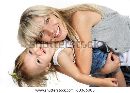 Portrait of a beautiful young family - mother and her baby smiling. Mother and little daughter in denim