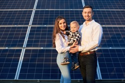 Portrait of a beautiful young family, smiling, standing together near photovoltaic solar module on a sunny day, front view, modern family concept